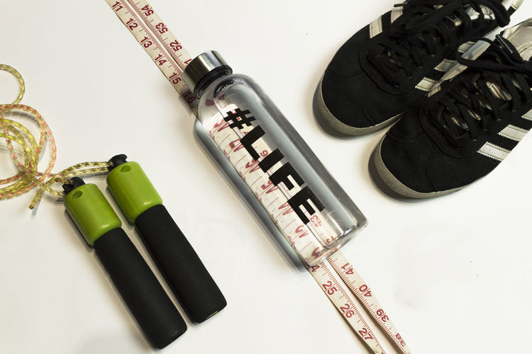 sport concept flat lay No People Still Life Traning Diet Flatlay Top View Flat Lay Workout Runing Sport Day Fitness Weightloss Indoors  Composition Close-up White Background Dumbbell Sneakers Measure Tape Active Lifestyles