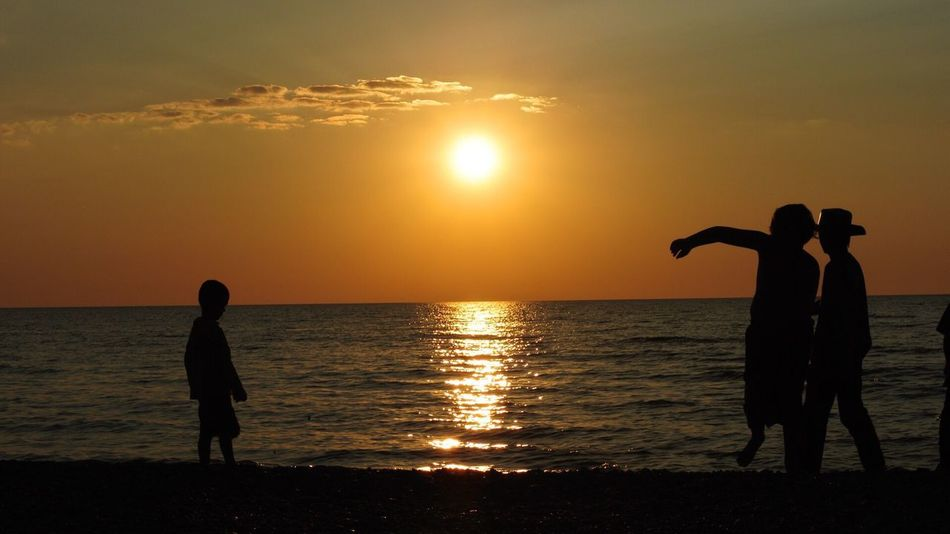 Kids throwing beach stones before the sunset Kids Being Kids Kids Playing At The Beach Sunset Silhouette Sea Water Beauty In Nature Sun Scenics Orange Color Nature Horizon Over Water Real People Beach Sky Lifestyles Leisure Activity Reflection Sunlight Standing