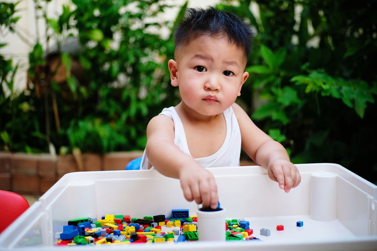 Portrait of cute baby boy playing with toys in yard