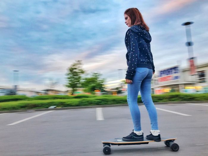 Low Angle View Of Woman Skateboarding On Road