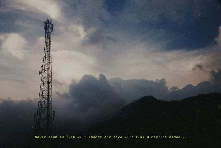 Low angle view of communications tower on field against sky