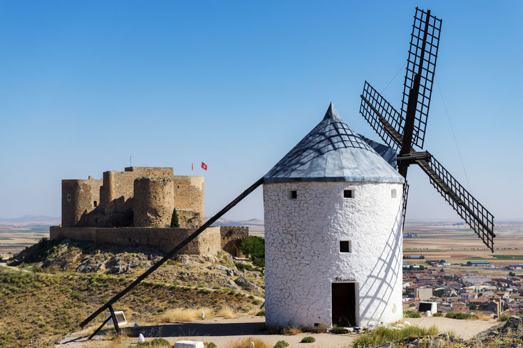 Spanish windmills, like those described in Cervantes's Don Quixote Consuegra Don Quijote Don Quichote SPAIN Windmill Blue Clear Sky Day Don Quixote And Sancho Panza Don Quijote And The Windmill Don Quijote De La Mancha Don Quijote Y Sancho Panza Don Quixote Mill Nature No People Outdoors Sky Spaın