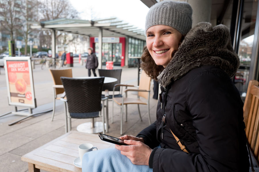 Portrait of smiling middle aged woman using smartphone in street cafe in Europe, Germany Adult Adults Only Communication Connection Day Holding Internet Knit Hat Leisure Activity One Person One Woman Only One Young Woman Only Only Women Outdoors People Portable Information Device Sitting Street Cafe Streetphotography Streetview Technology Warm Clothing Winter Wireless Technology Young Adult