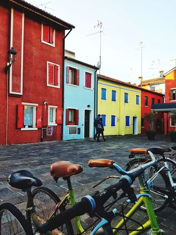 Bicycle Building Exterior Cycling Transportation Built Structure Mountain Bike Multi Colored Houses Town Street People Walking On The Street Coloured Houses in Caorle Italy