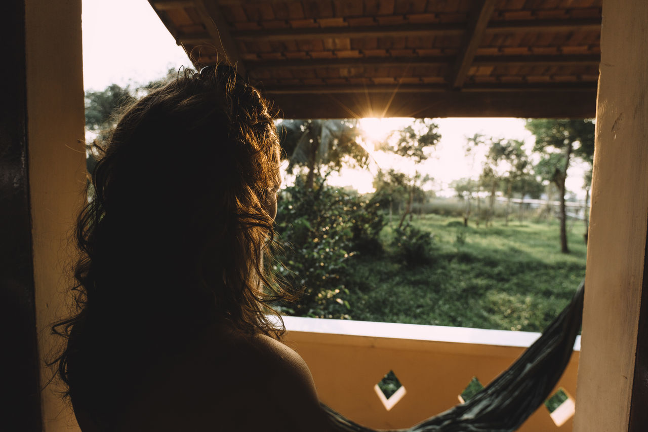 Rear view of woman standing by window during sunset