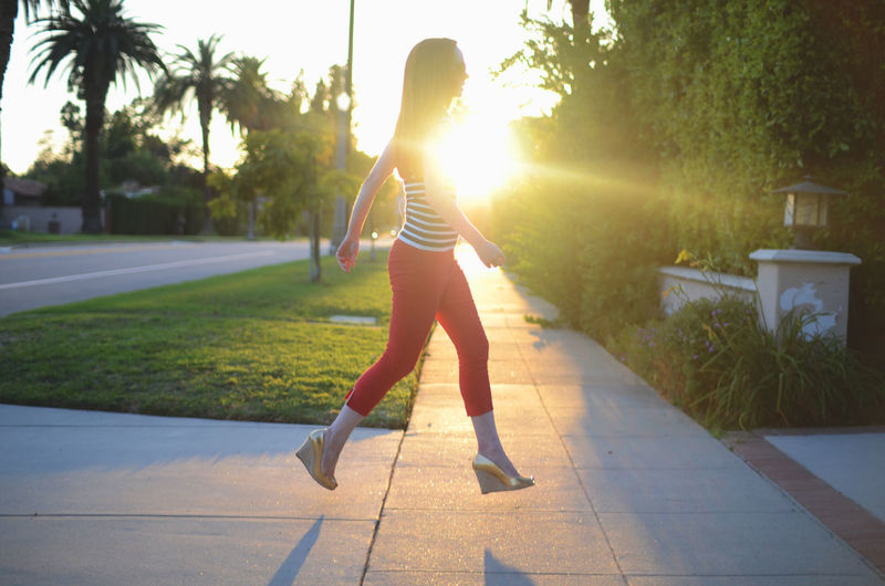 Full length side view of woman walking on footpath during sunny day