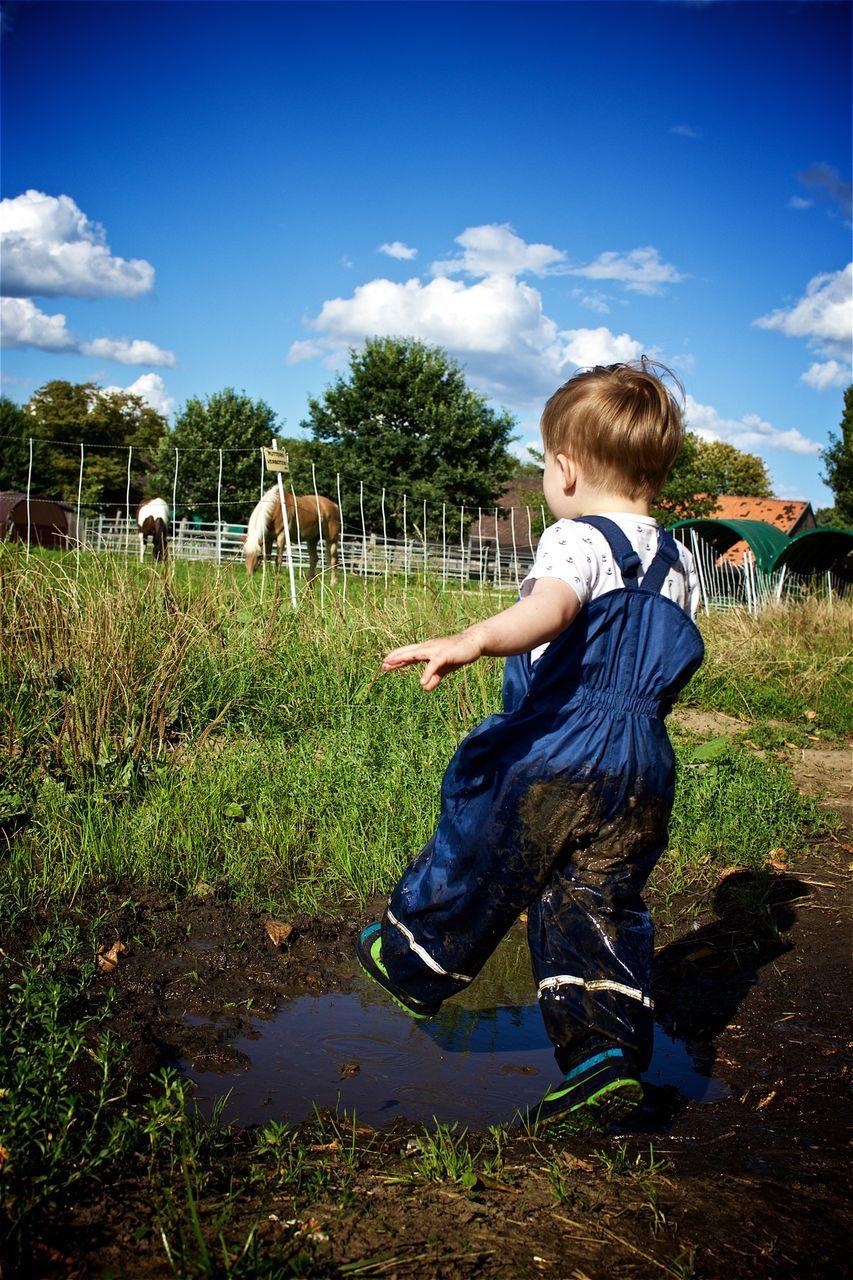 Full Length Of Boy Splashing Mud On Field Against Sky