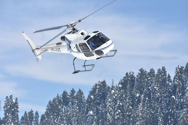 A chopper carrying tourists to the higher reaches at Gulmarg takes off during sunshine on Monday Srinagar Kashmir Kashmir Gulmarq Tree Forest Business Finance And Industry Sky Helicopter
