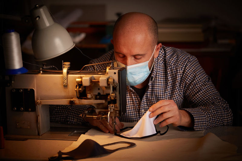 Man sewing mask with machine on table