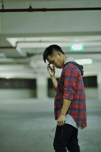 Side view of thoughtful man standing at parking lot