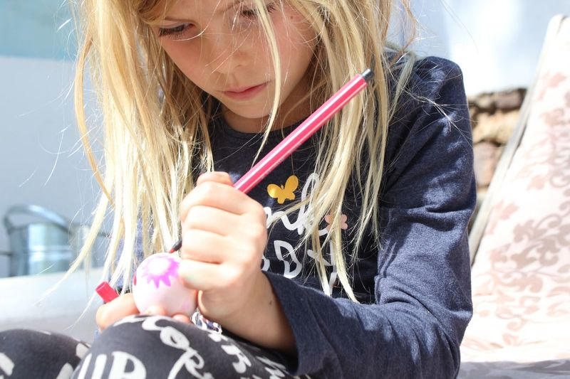 Close-Up Of Girl Painting Easter Egg