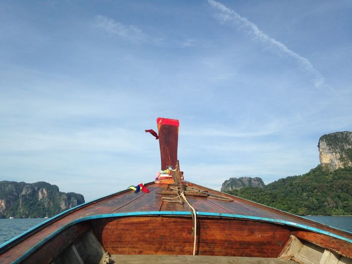 Cropped image of boat on lake against blue sky during sunny day