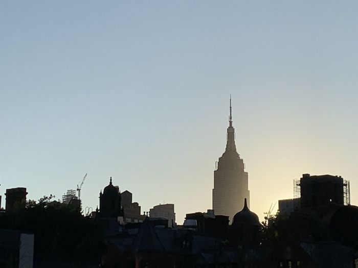 Silhouette of buildings in city against clear sky