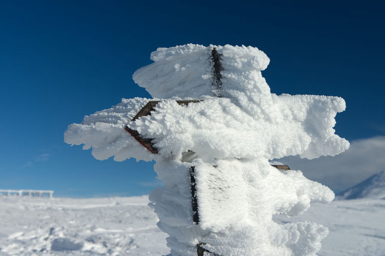 Close-up of snow against clear blue sky