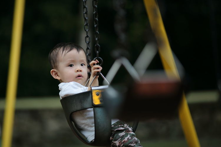 Side View Portrait Of Boy Sitting On Swing At Playground
