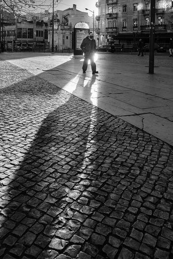Shadow of man walking on street in city