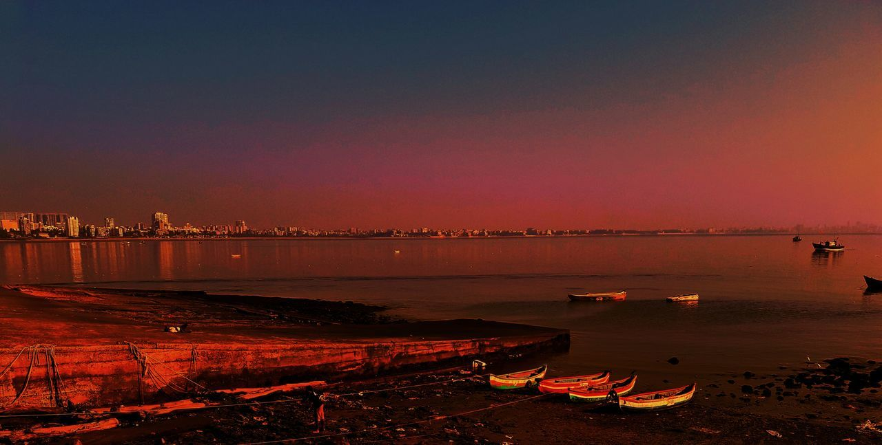 sunset, water, dusk, sky, night, nature, outdoors, no people, beauty in nature, sea, beach, scenics, illuminated, clear sky, architecture, city