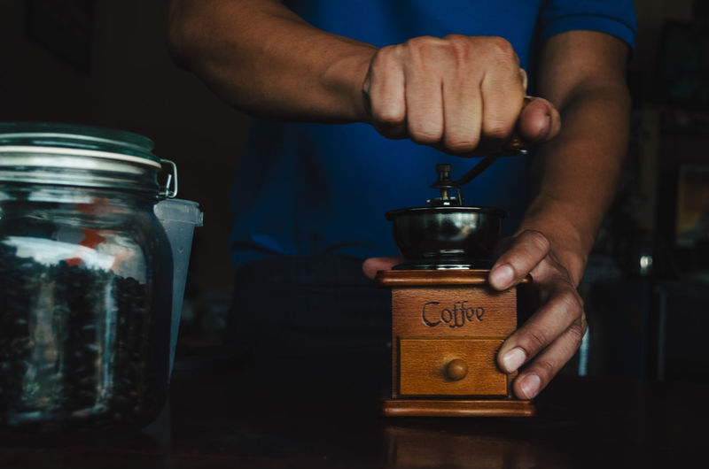Midsection Of Man Grinding Beans In Coffee Grinder On Table