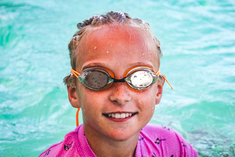 portrait of a young girl wearing swimming goggles poolside in summertime Headshot Portrait One Person Child Smiling Childhood Real People Front View Close-up Water Looking At Camera Leisure Activity Day Lifestyles Happiness Emotion Outdoors Swimming Pool Innocence Eyewear Swimming Goggles Girls Poolside