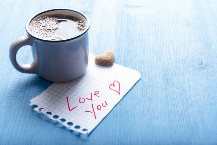 Hot coffee in an antique cup, heart shaped sugar and a piece math paper with the words love you on it, on a blue background under morning light. Breakfast Wooden Table Blue Table Break Time Coffee - Drink Communication Comunication Day Drink Hot Coffee Love You Messages Morning Routine No People Text Warm Drink