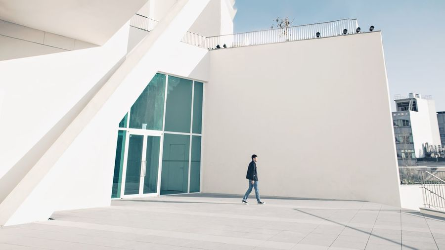 Rear view of man walking by building against clear sky