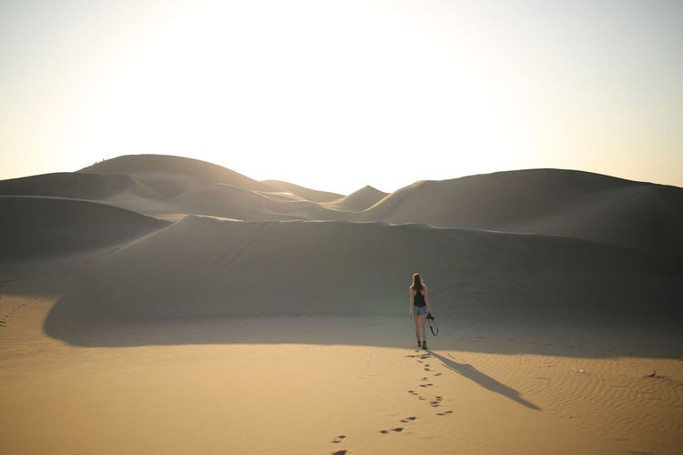Woman walking in desert in Peru Land Desert Sky Sand One Person Nature Scenics - Nature Tranquil Scene Real People Sand Dune Full Length Tranquility Leisure Activity Remote Landscape Arid Climate Beauty In Nature Walking Mountain Lifestyles Climate Woman Peru Travel Shadow