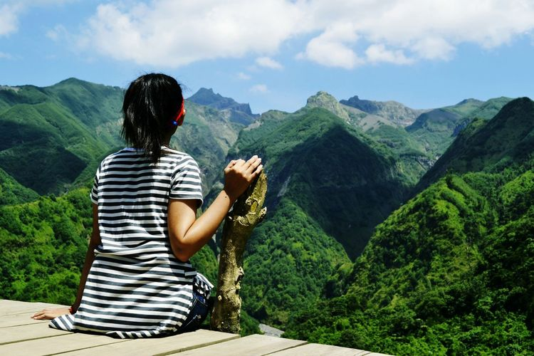 Rear view of woman looking at mountains while sitting on observation point
