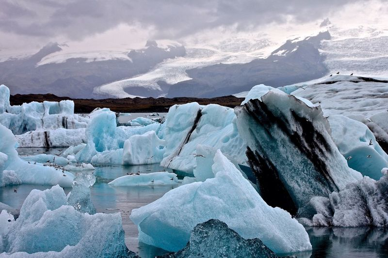 Icebergs Floating On Sea By Snow Covered Mountains Against Sky