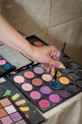 Close-Up Of Woman Hand Holding Make-Up Brush Over Palette