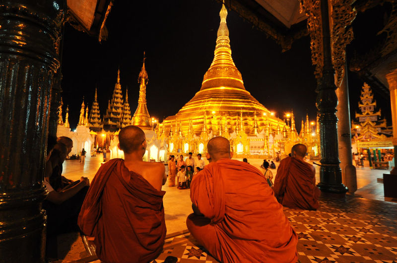 Monks sitting in front of shwedagon pagoda at night