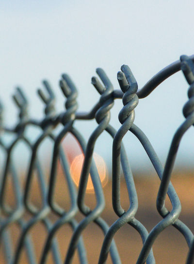 Chainlink fence near railroad tracks Chainlink Fence Clear Sky Close-up Day Evening Metal No People Outdoors Pattern Safety