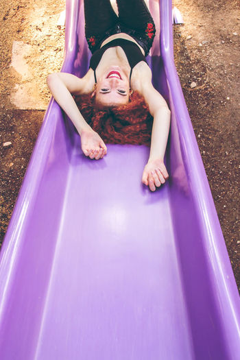 High Angle Portrait Of Young Woman Sliding On Purple Slide In Playground