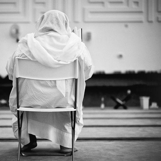Rear view of a Jain nun sitting on chair