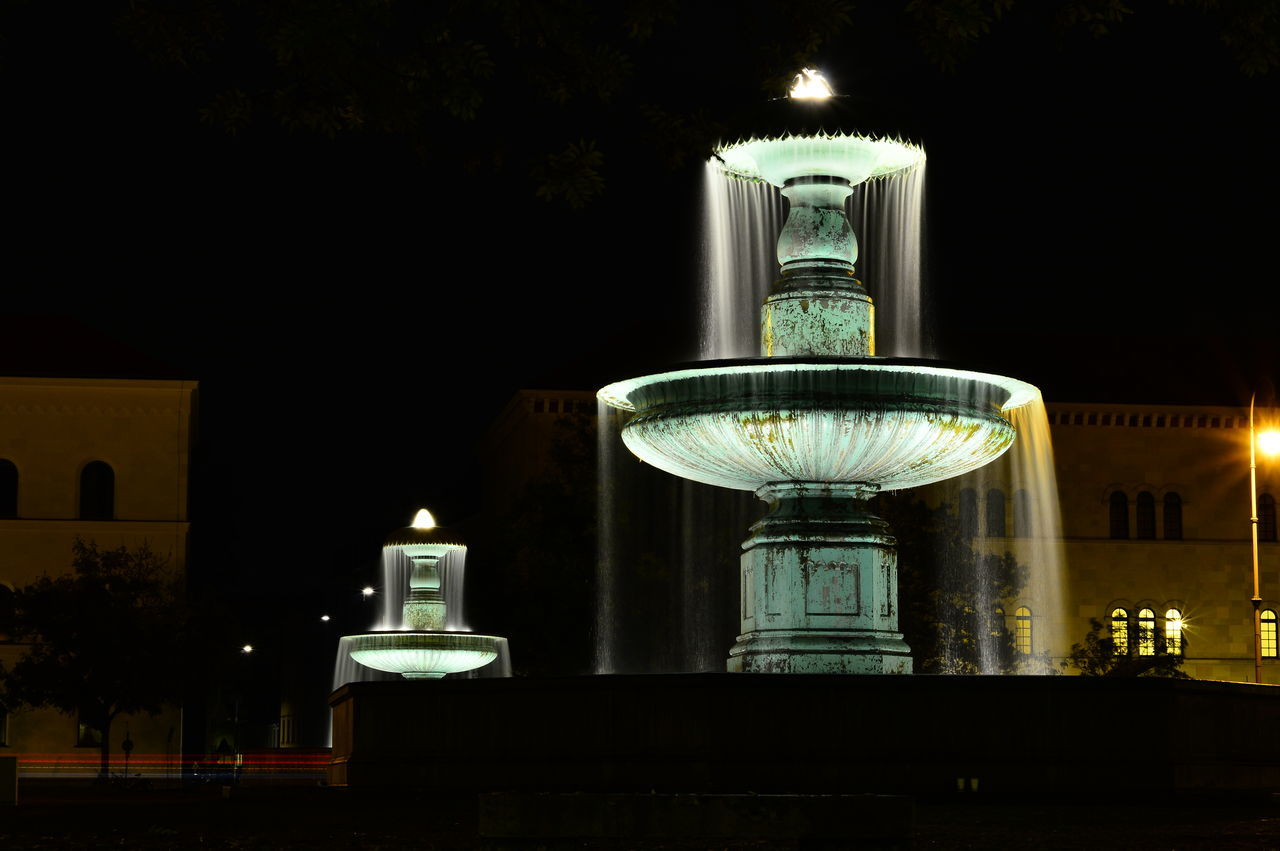 Fountain Against Building At Night