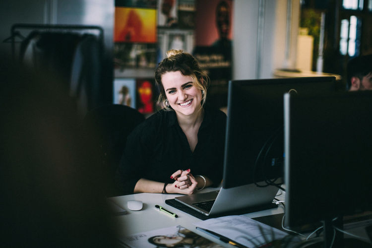 Portrait young woman smiling while sitting at desk in creative office