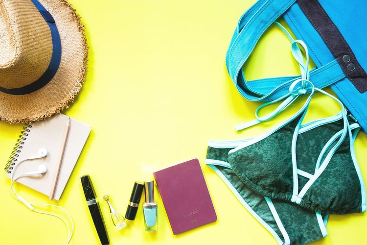 Close-up of bikini with purse and hat on yellow background