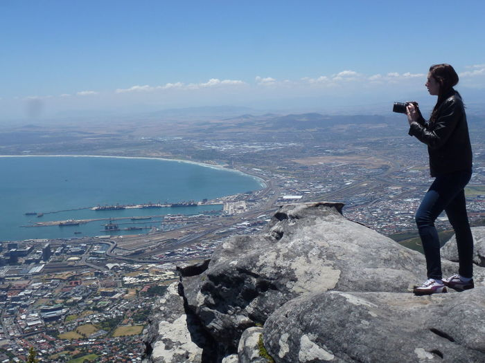 Woman Photographing Through Camera While Standing On Mountain Against Sky