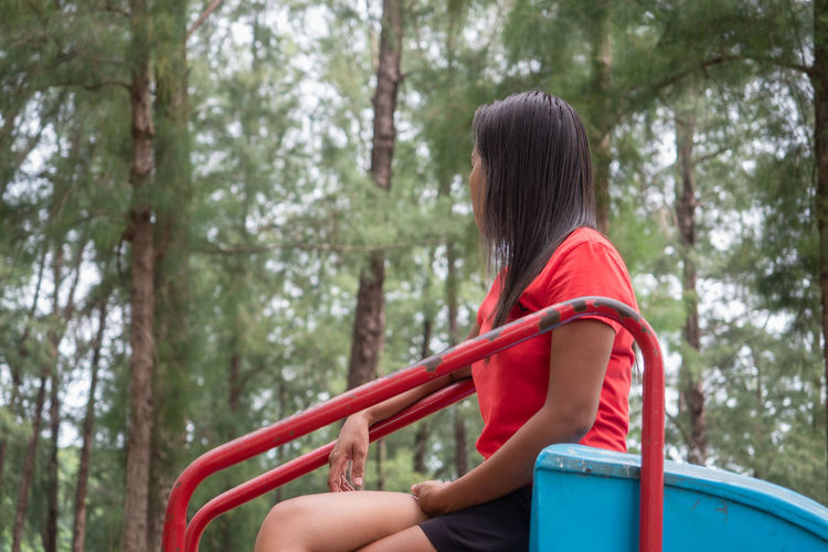 Rear view of woman sitting on slide in playground