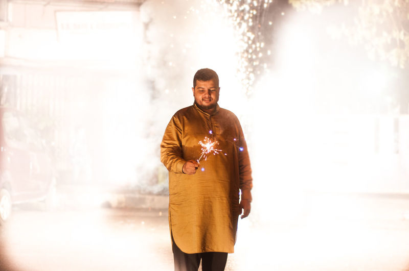 Man holding lit sparkler while standing at night during diwali