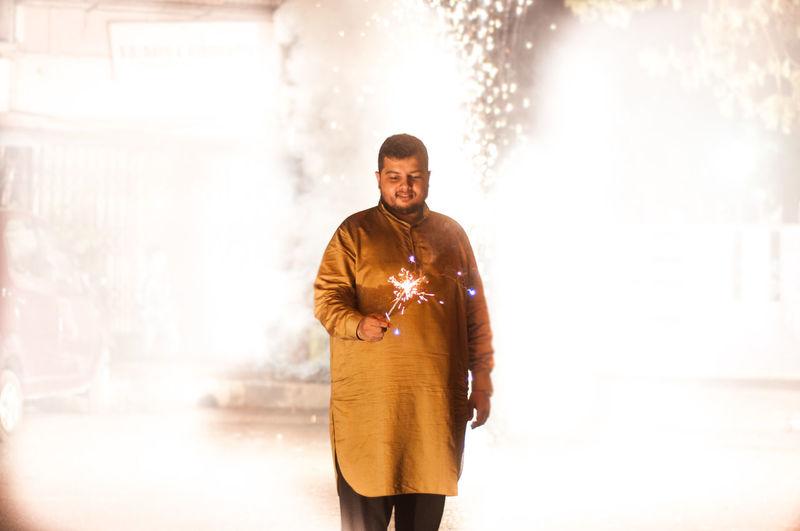 Man holding lit sparkler while standing at night during diwali
