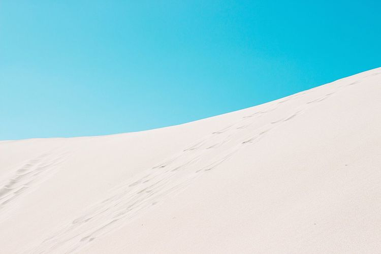 Low Angle View Of Sand Dune In Desert Against Clear Sky
