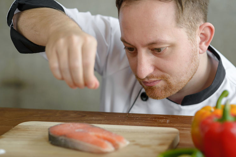 Close-up of man sprinkling spice on fish