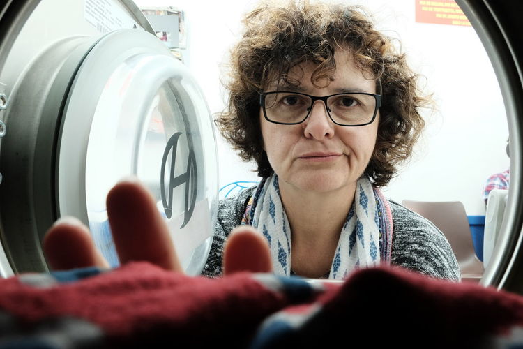 Portrait of mature woman removing laundry from washing machine