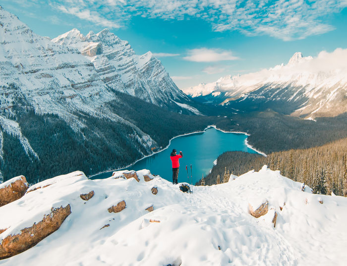 A lone figure in a red coat taking a photo of Peyto Lake after a first winter snow Winter Precipice Camping Dare Point Of View Edge Mountain Scenics - Nature Cold Temperature Beauty In Nature Snow Mountain Range Snowcapped Mountain Sky Tranquil Scene Cloud - Sky Nature Non-urban Scene Tranquility Environment Day Landscape Idyllic White Color No People Mountain Peak