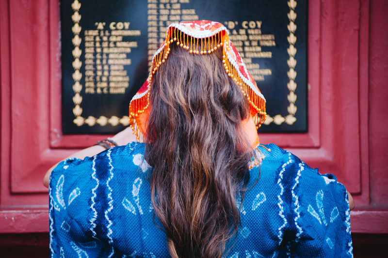 Rear view of young woman standing in front of blackboard