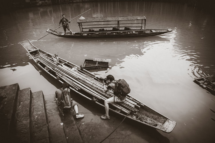 Traveler take a photo at the river of Phoenix Ancient Town (Fenghuang) The Street Photographer - 2018 EyeEm Awards Day Group Of People High Angle View Lake Lifestyles Men Mode Of Transportation Moored Nature Nautical Vessel Occupation Outdoors People Real People Reflection Sitting Transportation Travel Travel Destinations Traverler Water