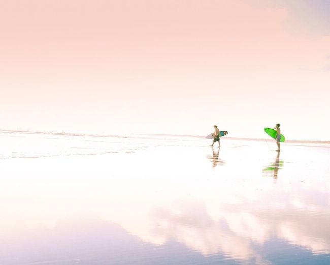Men with surfboards walking on seashore at beach against sky