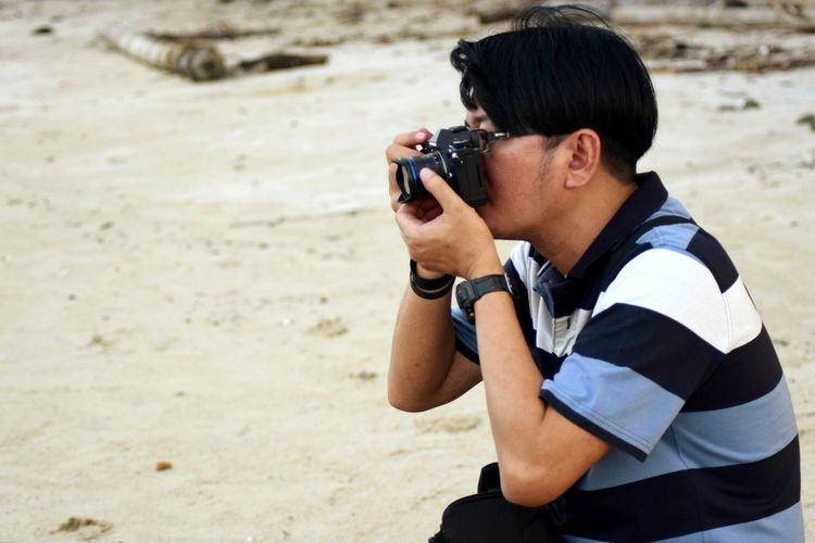 Side view of young man photographing at beach
