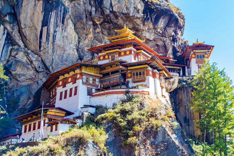 ASIA Architecture Buddhist Monastery Taktsang Tiger's Nest Architecture Belief Bhutan Buddhism Building Building Exterior Built Structure Cliff Day Heritage Low Angle View Nature No People Outdoors Paro Paro Taktsang Place Of Worship Plant Religion Rock Rock - Object Shrine Solid Temple Tigers Nest Traditional Travel Travel Destinations Tree World Wonder