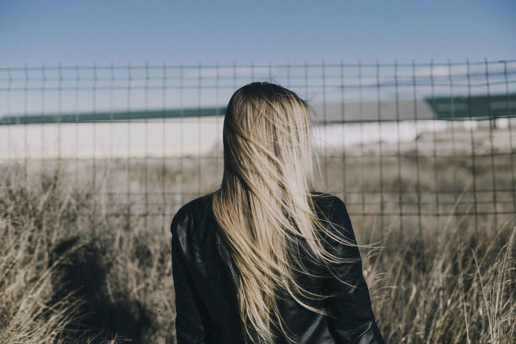 Backyard Faceless Backgrounds Black Jacket Blond Hair Day Fence Focus On Foreground Lifestyles Long Hair Nature One Person One Woman Only Outdoors People Real People Rear View Sky Wind Women Young Women